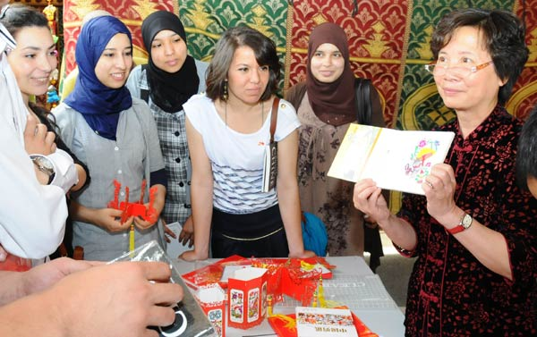 Yang Gang (right), director of the Confucius Institute at the University Mohammed V-Agdal in Morocco, introduces local students to Chinese paper-cuts on April 16. [Lin Feng / Xinhua]
