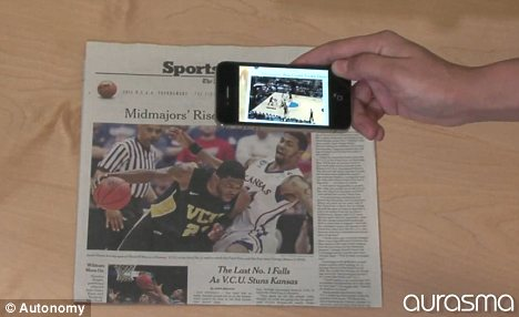 A smartphone with aurasma software will play sports footage when pointed at a newspaper photo of a recent match.