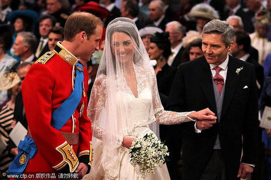 Prince William speaks to his bride, Catherine Middleton as she holds the hand of her father Michael Middleton at Westminster Abbey on April 29, 2011 in London.