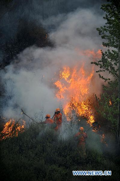 Firefighters extinguish fire in a forest that borders the cities of Jingzhong and Yangquan, north China's Shanxi Province, April 30, 2011. The fire started at about 9 p.m. on Friday. No casualties have been reported as of Saturday noon. The battle against the blaze is still underway.