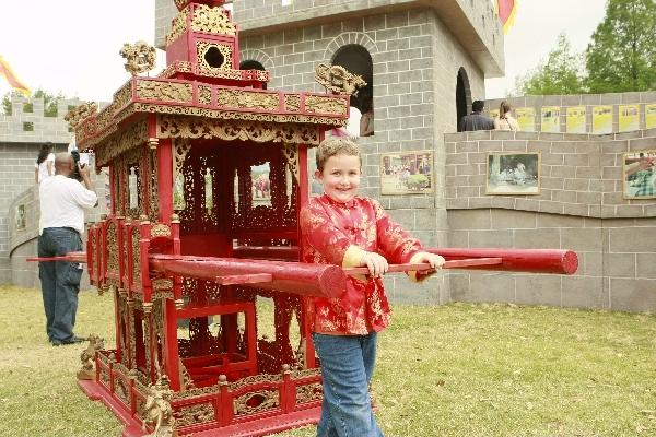 A boy in traditional Chinese costume tries to carry a sedan chair during the 2011 Houston International Festival in Houston, the United States, April 30, 2011.
