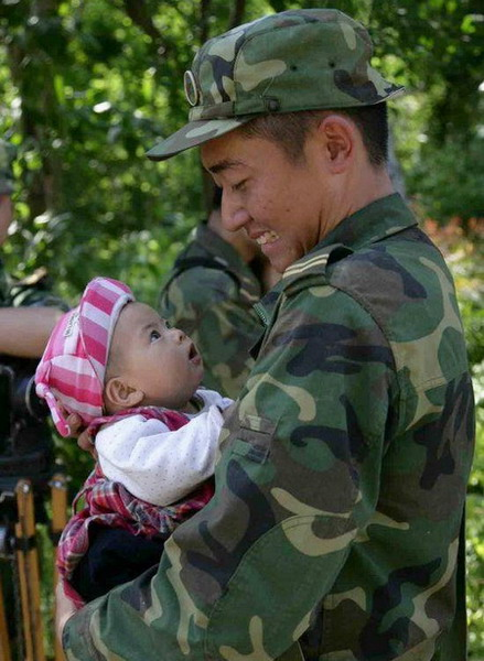 A loyal solider and an innocent child stare at each other. The solider took the baby from its grandmother while walking across a bridge on the afternoon of May 14. He carried the child for 1.5 kilometers to safety. The May 12 earthquake caused heavy casualties and inflicted psychological trauma on numerous victims. [People's Daily]