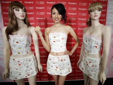 The white, bustier-style garment and matching skirt by Triumph are covered with messages from 36 different countries received in the aftermath of the disaster, each accompanied by a tiny flag of the nation that sent it.
