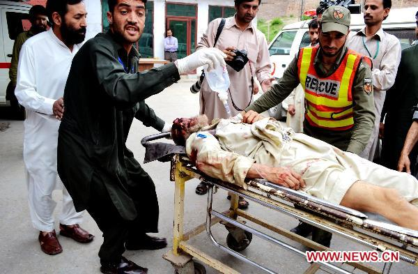 People transfer an injured man to a hospital in northwest Pakistan's Peshawar, May 13, 2011. At least 80 people were killed and dozens injured in a twin suicide blast that took place early Friday morning at a military training center in Charsadda, a city some 30 kilometers northeast of Peshawar in northwest Pakistan. [Xinhua/Umar Qayyum]