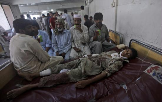 Relatives of a Pakistani youth who was injured in twin suicide bombs attacks in shabqadar, gather around his bed in a local hospital in Peshawar, Pakistan, Friday, May 13, 2011.[CNTV]