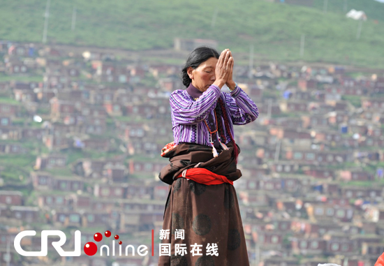 With eyes closed, a Tibetan woman prays with her palms putting together in front of her forehead. [Photo/CRI]