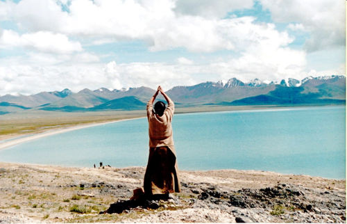 A Tibetan pilgrim prays besides a holy lake in Tibet with her palms putting together. [Photo/CRI]