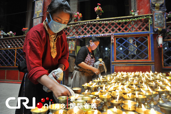 Tibetan pilgrims tidy up the table of butter lamps in a Tibetan monastery. [Photo/CRI] Butter lamp is one of the conspicuous symbols in Tibetan temples and monasteries.