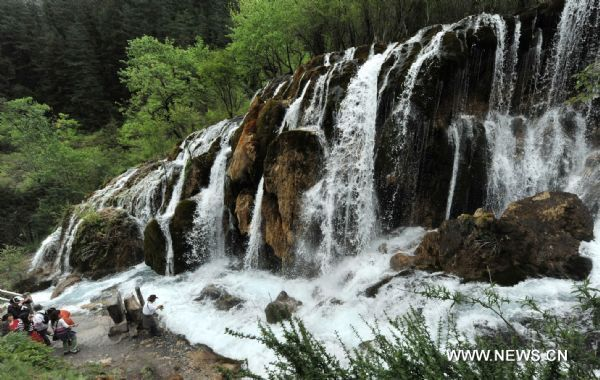 Tourists enjoy the scenery of a fall in the Jiuzhaigou scenery spot in southwest China's Sichuan Province, on May 18, 2011. After three years' remedy and recovery, Jiuzhaigou, a renowned resort once had been badly affected by a deadly earthquake, is booming in its tourism business, with the daily reception number reaching nearly 10,000 in May. (Xinhua/Chen Haining)