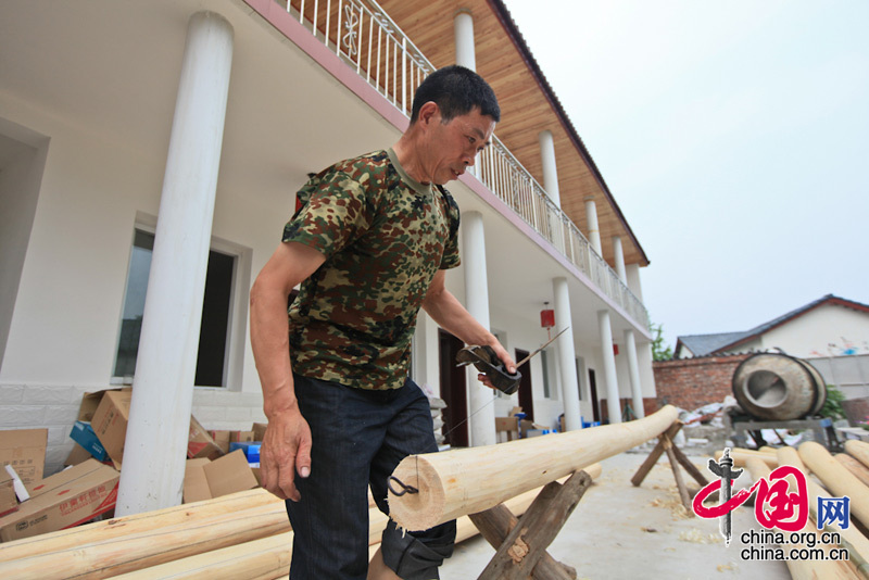Liu Jiahuai's own rural home inn is under construction.A 24-member reporting team headed by China International Publishing Group (CIPG) Vice President Lu Cairong (Central )pays a visit to Xinxing Town, Pengzhou City, severely hit by a devastating earthquake in 2008, to report the general condition of the house rebuilding program there.[Photo: Yang Jia/China.org.cn]