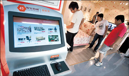 A computer screen displays various furniture items with their selling prices while Chinese shop inside the newlyopened Taobao Mall in Beijing. Taobao launched a five-story home furnishings showroom on Friday for customers to try out sofas, tables and other big-ticket items before placing an order online. [Shanghai Daily]