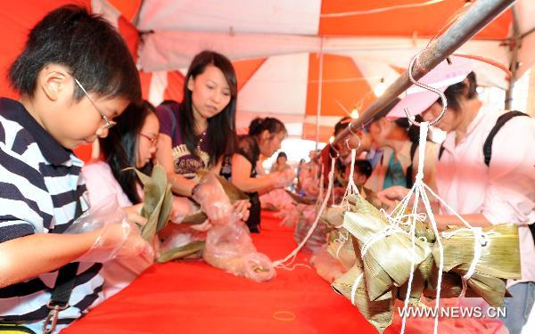 Citizens wrap zongzi, a pyramid-shaped dumpling made of glutinous rice wrapped in bamboo or reed leaves, at the traditional rice food festival held in Taipei, south China's Taiwan, May 29, 2011. A traditional rice food festival kicked off in Taipei on Sunday, attracting many citizens to taste delicious snacks.