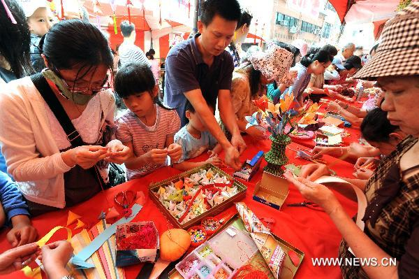 A girl learns to make handicraft at the traditional rice food festival held in Taipei, south China's Taiwan, May 29, 2011. A traditional rice food festival kicked off in Taipei on Sunday, attracting many citizens to taste delicious snacks.