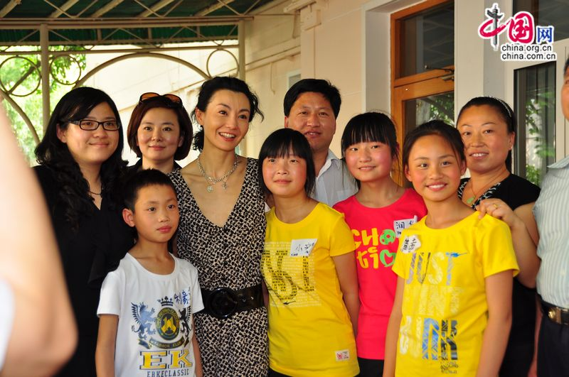 Maggie Cheung pose for photo with children from Henan Province who have been benefitted from UNICEF's child welfare programmes. [Pierre Chen / China.org.cn]