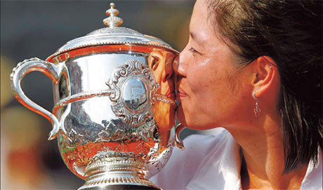 It's love at first sight for Li Na and the trophy she earned on Saturday. She beat Francesca Schiavone of Italy in the women's final of the French Open tennis tournament in Paris . [China Daily]