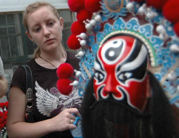 Katherine Jones, an American student studying in Liaocheng University looks at a Peking Opera mask in Liaocheng, east China's Shandong Province, June 9, 2011.