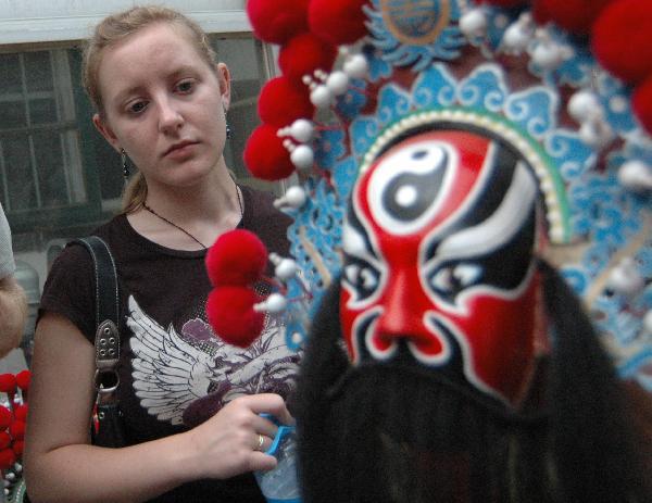 Katherine Jones, an American student studying in Liaocheng University looks at a Peking Opera mask in Liaocheng, east China's Shandong Province, June 9, 2011.