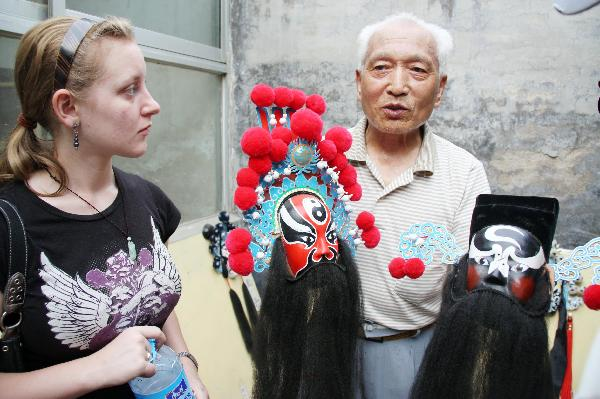 Katherine Jones, an American student studying in Liaocheng University listens to an introduction of a Peking Opera mask in Liaocheng, east China's Shandong Province, June 9, 2011.