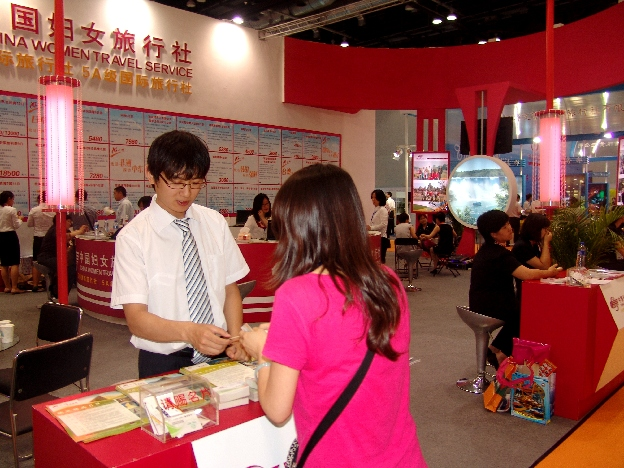 Women's Travel Agency—A man working for China Women Travel Service talks to a visitor.[China.org.cn]