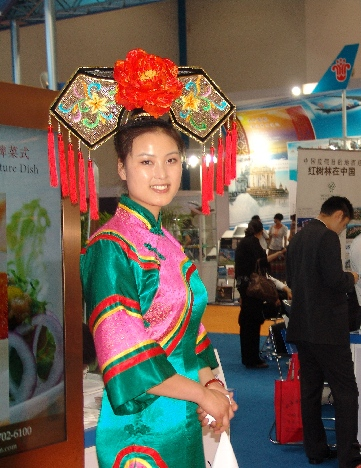 Headdress—A woman dressed in a traditional southern costume (!! I don't know if that's true!!_ invites passersby to China Southern's booth.