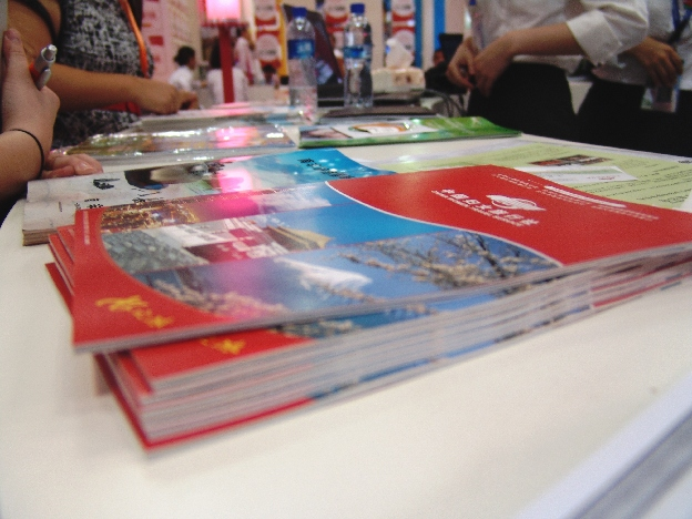 Brochures, women's travel—Booth visitors look at booklets and brochures at China Women Travel Service.[China.org.cn]