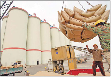Workers unload imported soybeans at a harbor in China. The country imported a record 54.8 million tons of soybeans in 2010, compared with 15.2 million tons of domestic production, General Administration of Customs data showed. [China Daily]