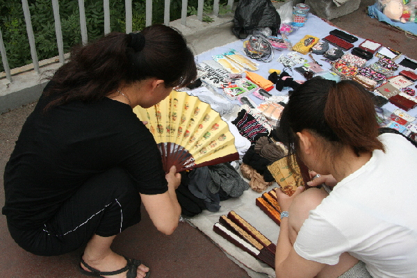Tang displays a fan to a customer at her spot on a pedestrian overpass. The fan sold for 12 yuan.