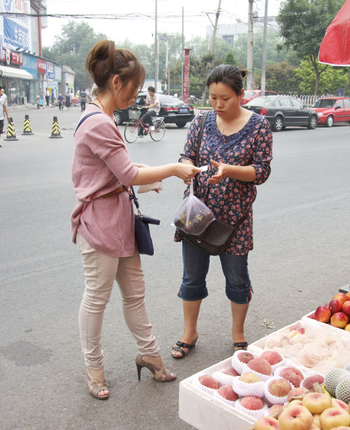 Lian Jing, a legal street vendor, gives a customer a bag of fruit for less than 20 yuan. She said she enjoys making friends with her customers who live in the neighborhood.