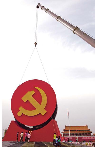 Workers place a giant emblem of the Communist Party of China (CPC) at Tian'anmen Square in Beijing on Monday. The emblem is part of a parterre being prepared to celebrate the 90th birthday of the CPC.