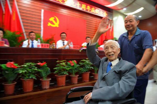 Huang Shu, the newest CPC member, waves during a CPC-joining ceremony at a hall in Huangshan, East China's Anhui province, June 28, 2011. [Photo/Xinhua]