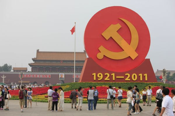 An emblem of the Communist Party of China (CPC) is seen surrounded by flowers on the Tiananmen Square in Beijing, capital of China, June 28, 2011.