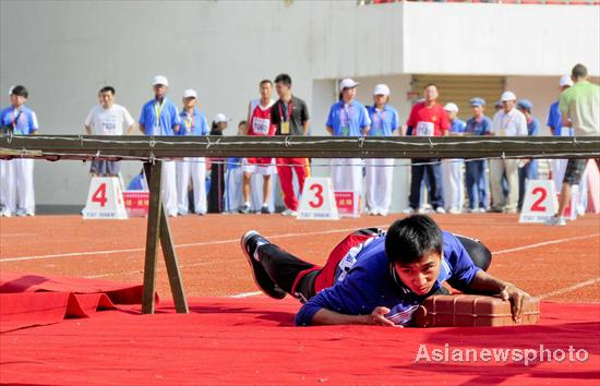 A competitor 'blows up a blockhouse' during the second national red sports meeting in Qingyang city, Northwest China's Gansu province, June 27, 2011.