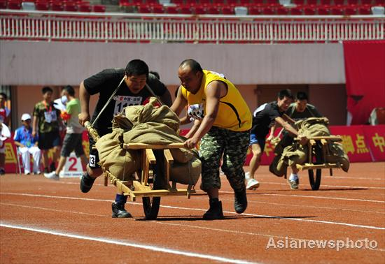 Competitors transport supplies using a one-wheel cart during the second national red sports meeting in Qingyang city, Northwest China's Gansu province, June 27, 2011.