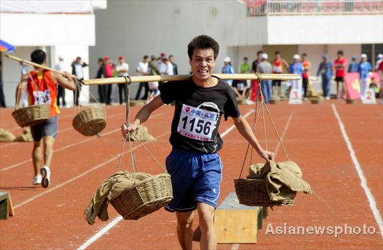 A competitor moves supplies using shoulder poles during the second national red sports meeting in Qingyang city, Northwest China's Gansu province, June 27, 2011.
