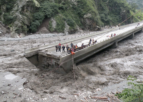 Part of a bridge in Yingxiu, Wenchuan county, Sichuan province, remains while another section has been washed out by mudslides triggered by torrential rain. Many people were trapped on the bridge on Monday. [Xinhua]