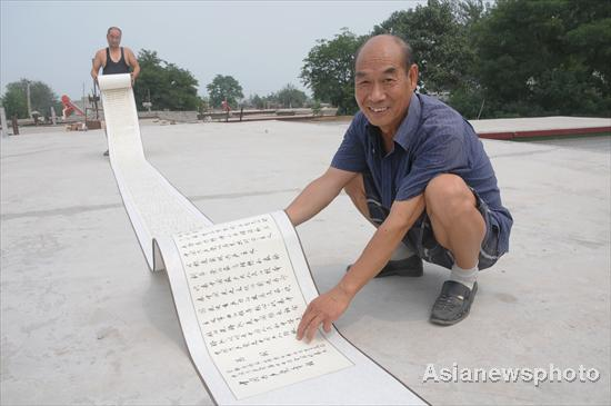 Niu Yinlu shows his calligraphy work &#8211; a scroll of the constitution of the Communist Party of China &#8211; in Hantai town, Xinle city, North China's Hebei province, July 14, 2011. 