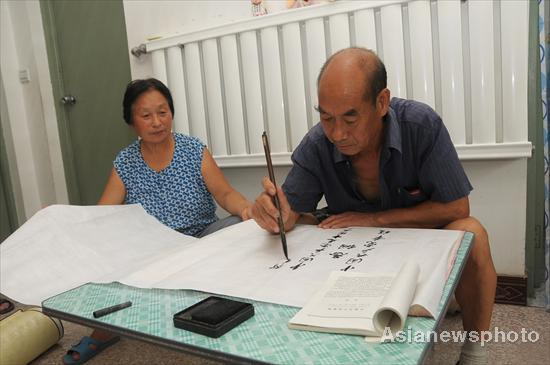 Niu Yinlu (R) practices calligraphy at home in Hantai town, Xinle city, North China's Hebei province, July 14, 2011.