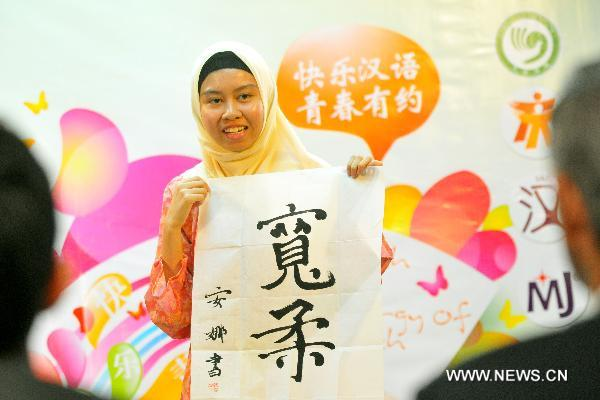 A contestant shows her calligraphy work during the Chinese language proficiency competition in Kuala Lumpur, Malaysia, on July 17, 2011. The Malaysian round of the Fourth 'Chinese Bridge' -- Chinese Proficiency Competition for High School Students took place here on Sunday with the participation of 16 contestants.