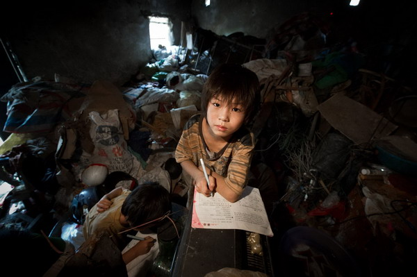 Sun Wanli does homework among rubbish in the family's house in Woyang county, East China's Anhui province, July 27, 2011. [Photo/Xinhua]