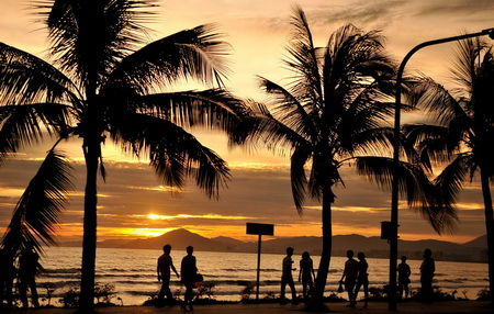 Tourists walk under sunset in Sanya city, south China's Hainan province, July 20, 2011.[