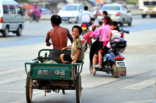 A 9-year-old boy named Xiong Sansan rides on the back of his father's tricycle to collect scraps in Baisha, an urban village in Liuzhou city, South China's Guangxi Zhuang autonomous region, July 29, 2011.