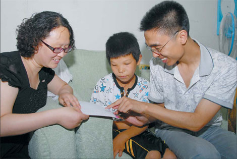 Xu Lina (left) and Duan Fei show 12-year-old Sun Tao how to use simple characters and pictures to communicate. Tao is deaf. Xu and Duan, founders of charity website baoen.cn, took Tao to the hospital in Shijiazhuang, Hebei province, to be evaluated for a hearing aid.