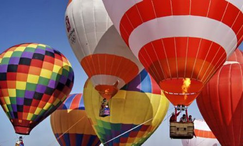 Tourists enjoy scenery during a hot-air balloon flying at a hot-air balloon festival in Guyang County, north China's Inner Mongolia Autonomous Region, Aug. 7, 2011.