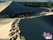Photo taken on Aug. 25, 2011 shows the adjacent Mingsha Mountain Dunes (Singing-Sand Dunes) in Dunhuang City, northwest China's Gansu Province.  The famous tourist attraction Mingsha Mountain Dunes, which is six kilometers south of Dunhuang City, has moved towards Yueya Spring for about 8 to 10 meters in the past 15 years due to the geological movement, according to the latest statistics. [China.org.cn]