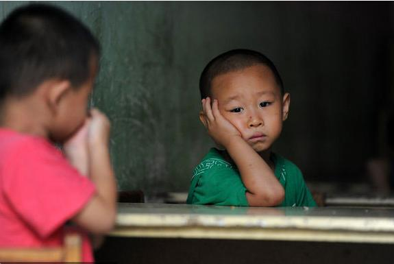 Two boys worry about their schooling for the coming semester in Beijing on August 15, 2011. Their primary school, where most pupils are the children of migrant workers, was demolished on August 10 after the contract between the school and local government ended.