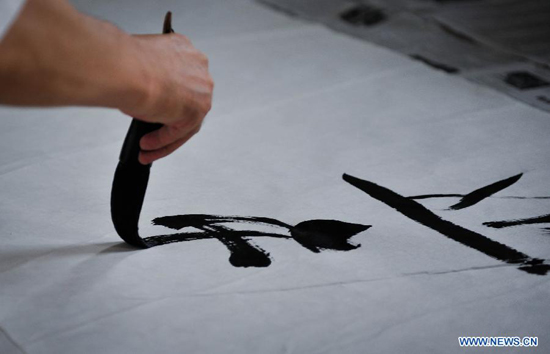 Chinese calligraphist Chen Jinchun performs at the opening ceremony of his exhibition 'Charm of the Chinese Calligraphy' in Palais des Nations, Geneva, Switzerland, Aug. 18, 2011.