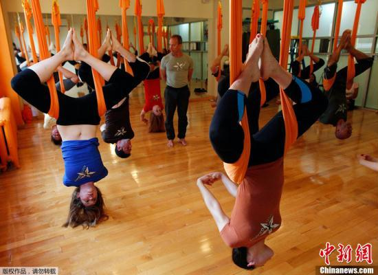 Suspended in air, yoga students are defying natural law to achieve a better body, mind and spirit. Called Anti-Gravity Yoga, this new form of exercise promises benefits that range from increased joint mobility to improved mental health.