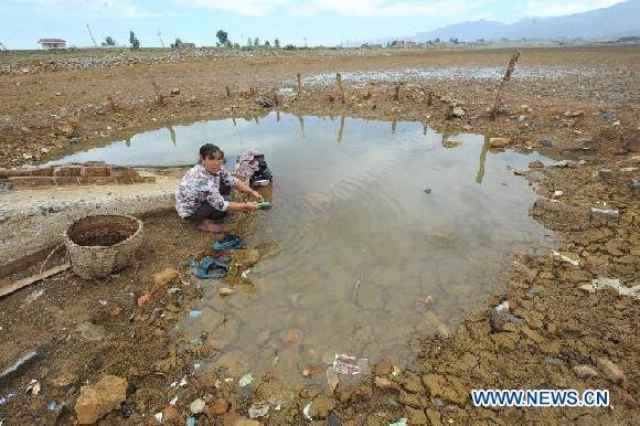 A housewife wash clothes at the dried-up Dongjin Reservior in Huangzhulin Village of Zhaotong City, southwest China's Yunnan Province, Aug. 23, 2011. [Xinhua]