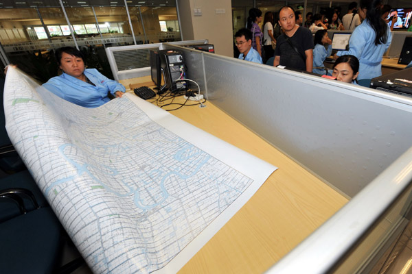 A worker at the National Geomatics Center of China in Beijing shows a map to visitors. China released its first 1:50,000 scale nationwide map on Thursday. [Photo/China Daily] 