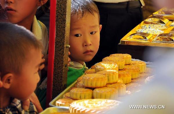 Children look at moon cakes during a moon cake feast in Shenchi, north China's Shanxi Province, Aug. 23, 2011.